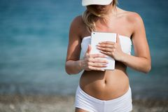 Young beautiful woman in sport suit is using her tablet on the beach.  Royalty Free Stock Images