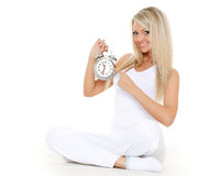 Young sporty woman  with alarm clock. Royalty Free Stock Photography