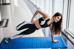 Young beautiful woman in sportswear doing side plank and looking at camera in front of window at gym royalty free stock images