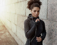 Young beautiful woman. In sportswear with earphones on city street Stock Images