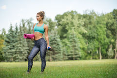 Young beautiful woman in sportswear. She`s holding a training mat. Going to do sports training. Gymnastics. Outdoors summer royalty free stock image