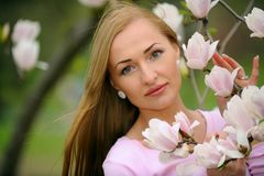 Young beautiful woman in spring blossom trees. Stock Photo