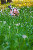 Young woman blowing a dandelion on fields Stock Photography