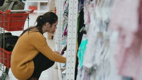 Young beautiful woman squatting in the supermarket and choosing baby clothes at showcase. Near female shopping cart. 4K stock footage