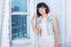 Young beautiful woman standing against a window with white curtains. Stock Image