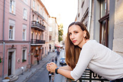 Young beautiful woman standing on the balcony. And looking out on street of european city Royalty Free Stock Images