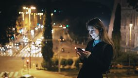 Young beautiful woman standing in the city centre near the Colosseum in Rome, Italy and using the smartphone. Stylish female near the traffic road browsing the Stock Photos