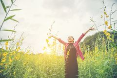 Young beautiful woman standing in the flower field enjoyment. Young beautiful woman standing in the flower field enjoyment background Royalty Free Stock Photo