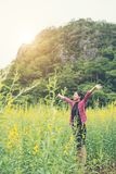 Young beautiful woman standing in the flower field enjoyment. Young beautiful woman standing in the flower field enjoyment background Stock Photo