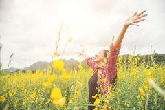 Young beautiful woman standing in the flower field enjoyment. Young beautiful woman standing in the flower field enjoyment background Stock Image