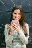 Young beautiful woman standing in front a blackboard wall. Stock Image