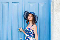 Young beautiful woman standing in front of a blue vintage entrance door Stock Image