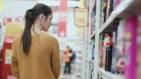 Young beautiful woman standing in front of shelves with household chemicals, holding one and try to choose. 4K stock video footage