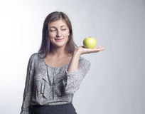 Young beautiful woman standing with green apple in hands. Young beautiful woman standing with a green apple in his hand and looking at him with a smile Stock Photo