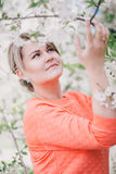 Young beautiful woman standing near blooming white cherry tree Stock Photos