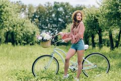 Young beautiful woman standing near retro bicycle with wicker basket full of flowers. In forest royalty free stock images