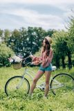 Young beautiful woman standing near retro bicycle with wicker basket full of flowers. In forest stock image