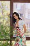 Young beautiful woman standing near the window Stock Photo