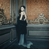 Young beautiful woman standing in the palace room Royalty Free Stock Image