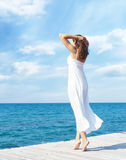 Young beautiful woman standing on a pier at summer.  Vacation, t Royalty Free Stock Image