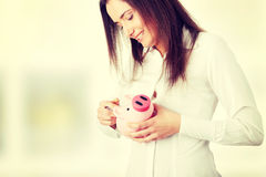 Young beautiful woman standing with piggy bank Stock Photography