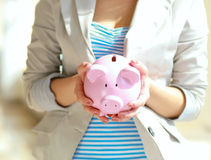 Young beautiful woman standing with piggy bank ( Royalty Free Stock Photos
