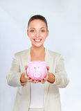 Young beautiful woman standing with piggy bank (money box) Royalty Free Stock Photography