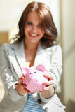 Young beautiful woman standing with piggy bank Royalty Free Stock Photo