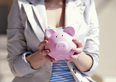 Young beautiful woman standing with piggy bank ( Royalty Free Stock Images