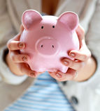 Young beautiful woman standing with piggy bank ( Royalty Free Stock Photo