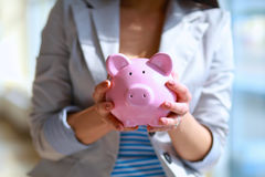 Young beautiful woman standing with piggy bank money box, on building Royalty Free Stock Photo