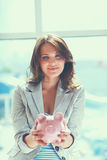 Young beautiful woman standing with piggy bank money box, on building Royalty Free Stock Image