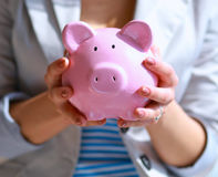 Young beautiful woman standing with piggy bank money box, on building Stock Images