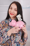 Young beautiful woman standing with piggy bank money box Royalty Free Stock Photos