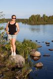 Young beautiful Caucasian woman standing on stone near lake water Royalty Free Stock Photography