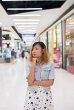 Young beautiful woman standing thinking something at shopping ma. Ll background Royalty Free Stock Images