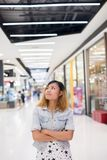 Young beautiful woman standing thinking something at shopping ma. Ll background Royalty Free Stock Image