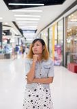 Young beautiful woman standing thinking something at shopping ma. Ll background Royalty Free Stock Photography