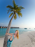 Young beautiful woman stands near palm tree against the tropical island Stock Image