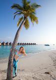 Young beautiful woman stands near palm tree, Maldives.Sea tropical landscape Royalty Free Stock Images