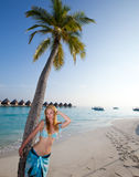 Young beautiful woman stands near palm tree, Maldives.Sea tropical landscape in a sunny day Royalty Free Stock Photos