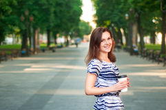 Young beautiful woman staying in the park with the coffee in her Stock Images