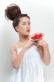 Young beautiful woman with strawberry. Young beautiful woman in white dress holding saucer with strawberry stock photography