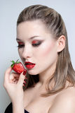 Young beautiful woman with strawberry. Portrait of young beautiful woman with strawberry royalty free stock photo