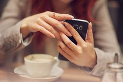 Young beautiful woman in a street cafe, is busy with her cell phone, close up at hands holding mobile phone royalty free stock images