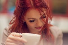 Young beautiful woman in a street cafe enjoying a coffee, is busy with her cell phone. Young beautiful woman in a street cafe enjoying a coffee, summerly urban Stock Images