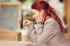 Young beautiful woman in a street cafe enjoying a coffee, summerly urban mood Royalty Free Stock Image