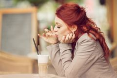 Young beautiful woman in a street cafe enjoying a coffee, summerly urban mood Royalty Free Stock Photo