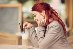 Young beautiful woman in a street cafe enjoying a coffee, summerly urban mood Stock Photography