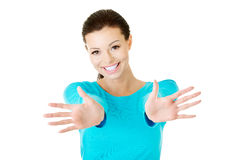 Young beautiful woman with stretched hands and showing her palms Stock Image